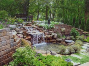 Backyard retaining wall with waterfall and pond.