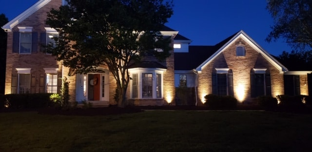 Landscape lighting along the front of a tan brick home with a red front door.