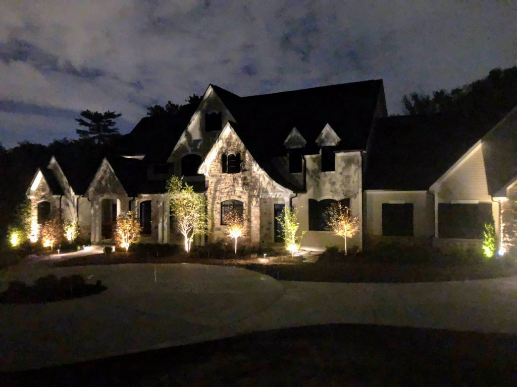 Low voltage landscape lighting uplighting trees in front of a brown home.