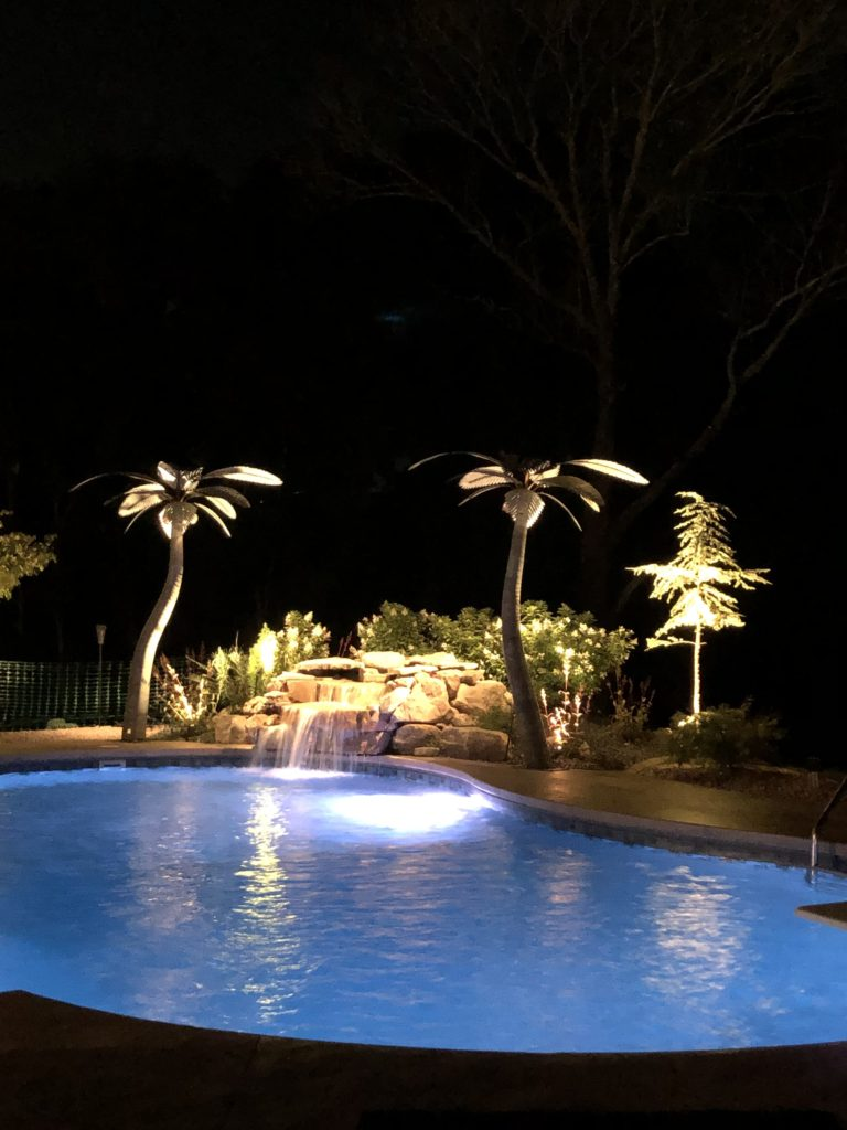 Dramatic outdoor landscape lighting around a waterfall and large, metal palm trees next to a pool.